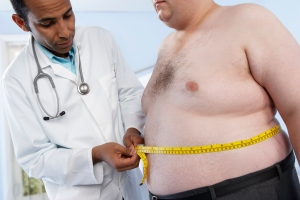 General practitioner measuring waist of obese patient